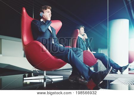 Smiling businessman in formal suit is sitting relaxed in chillout area of modern office interior on red curved armchair next to mirror and having phone conversation with his colleague