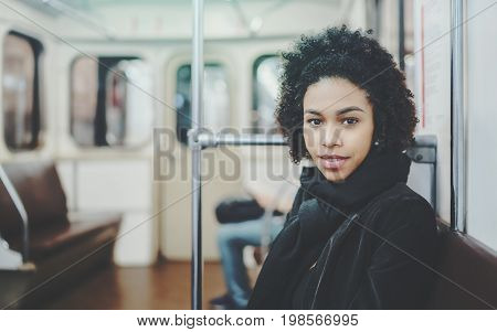 Portrait of young curly partly smiling afro american girl sitting on seat of carriage of subway electric train near grab-handle with copy space for text your logo or other advertising message