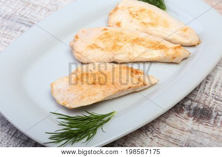 Slices of roasted chicken breast and tomato on white plate.