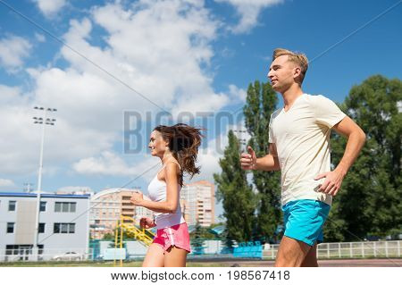 Sport and healthy fitness. Couple running on arena track. Coach and trainer at workout. Man and woman sunny outdoor on blue sky. Runner on competition and future success.