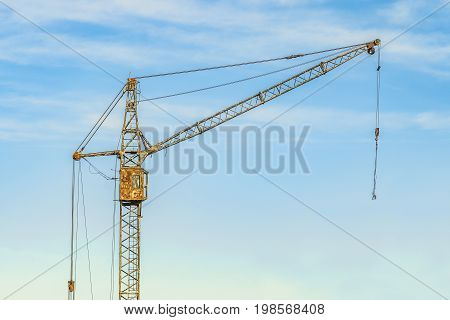 Old abandoned tower crane on a sky background