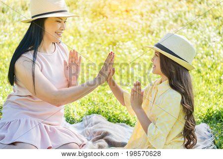 Happy mother and daughter are playing with hands while relaxing on meadow. They are looking at each other with joy and smiling