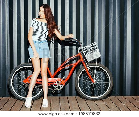 Beautiful long-haired leggy girl asian in summer outfit posing with a vintage red bicycle. Night shot. Look at camera. Outdoor.