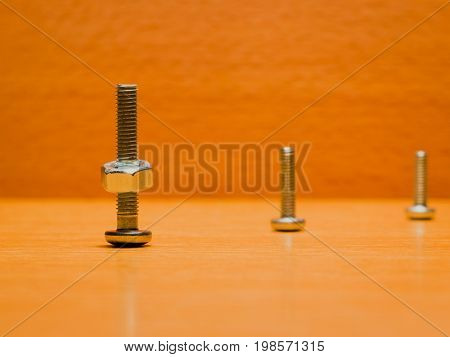 Three screws on a wooden background on one of them a nut is screwed on