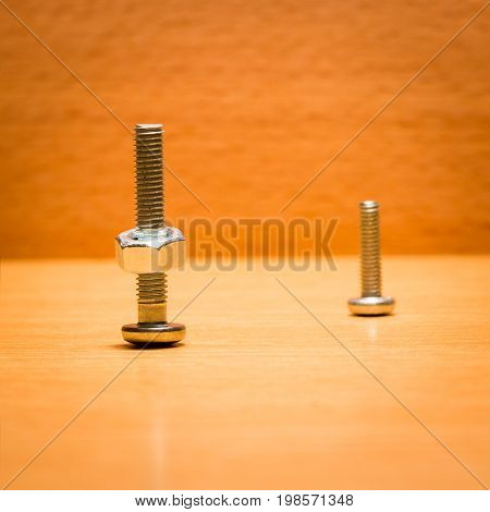 Two screws on a wooden background on one of them screwed nut small tools for fastening