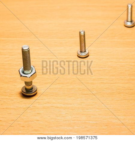 Three screws on a wooden surface located diagonally on one of them is screwed on a nut small and durable tools for fastening