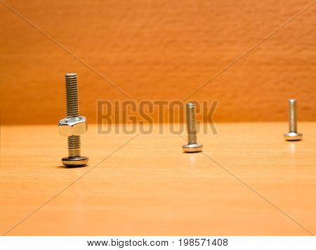 Three screws of different sizes on one of them are screwed a nut on a wooden background they are arranged diagonally
