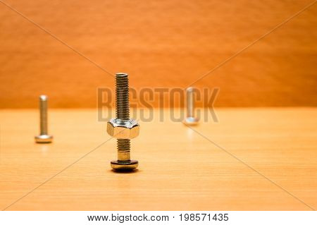 Three screws of different size on the wooden surface in the foreground the largest of which is screwed on the nut