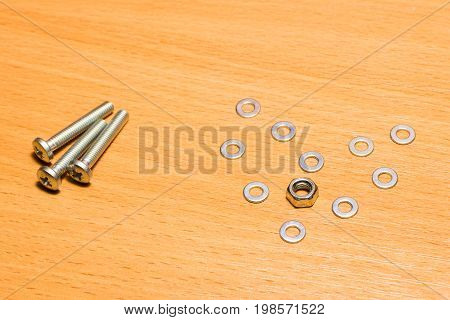 Heart of metal washers with a nut and screws on a wooden background a love symbol made of small tools for fastening