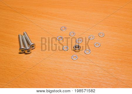 The heart of a love symbol laid out of small tools for fastening metal washers and nuts is also near the screws on a wooden surface