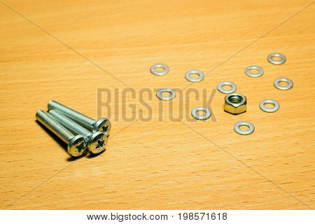 Three screws and heart made of metal washers and nuts on a wooden background