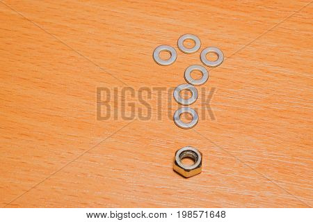 A question mark laid out of metal washers and nuts of small and durable tools for fastening on a wooden background