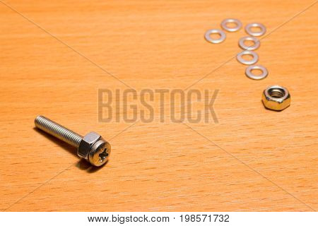 Screw and question mark small tools for fastening on a wooden background