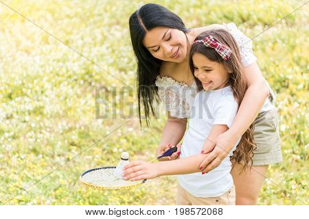 Cheerful woman is teaching her daughter to play tennis. She is adjusting her hand in correct position for pitch. Family is standing on meadow and smiling