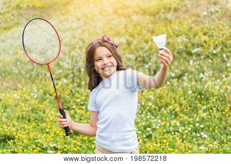 I like tennis. Waist up portrait of carefree little girl is ready to throw shuttlecock. She is raising racket and smiling. Child is standing on meadow