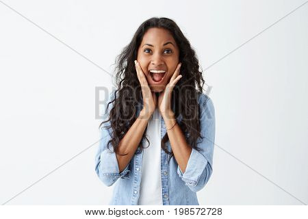Human facial expressions, emotions and feelings. Bug-eyed stylish young dark-skinned brunette woman in blue denim shirt exclaiming in shock, keeping hands on head, astonished with some unexpected news