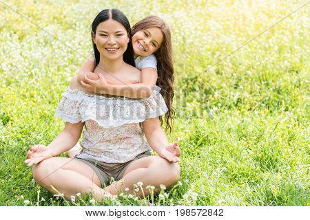 Portrait of happy woman mediating on meadow while her daughter is embracing her with love. They are looking at camera and smiling. Copy space in right side