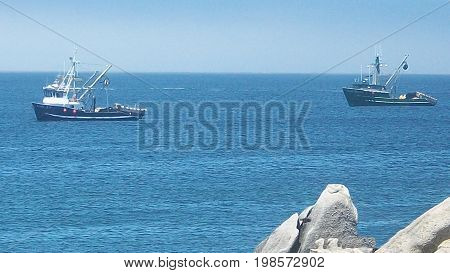 Two fishing boats in Monterey Bay California with rocks