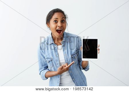Amazed young African-American young woman wearing blue shirt over white t-shirt holding tablet in her hands, showing how cool this tablet is, keeping mouth wide open, looking surprised.