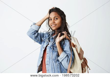 Portrait of cheerful beautiful dark-skinned woman with wavy hair having dark charming eyes and engaging smile posing in studio over white background, wearing denim jacket with backpack on her shoulder. People, emotions and lifestyle concept