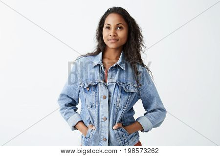 Portrait of young Afro-American girl with dark skin wearing denim jacket and red t-shirt looking at camera with serious expression, standing with her hands in pockets. Dark-skinned female model with dark hair posing indoors.