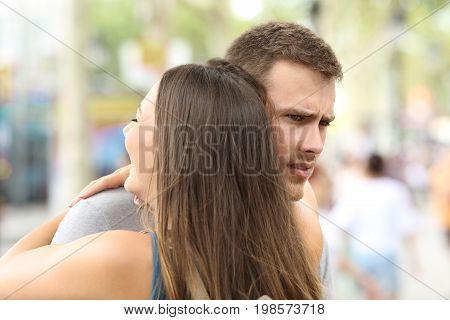 Discontent boyfriend hugging his partner on the street
