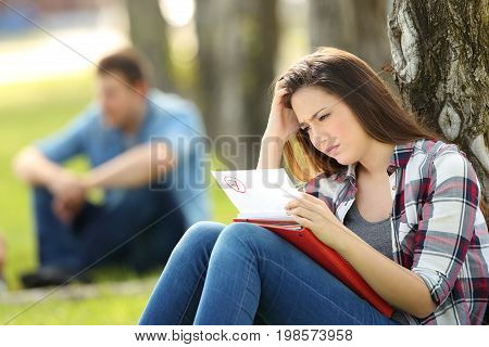 Single sad student looking at failed exam sitting on the grass in a park with unfocused people in the background