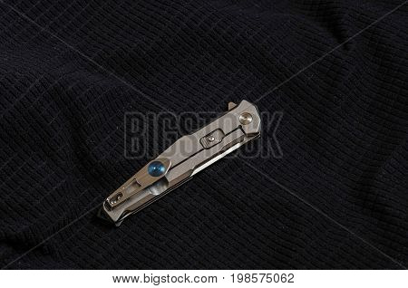 Knife With A Metal Handle In Folded Form On Black Textiles.