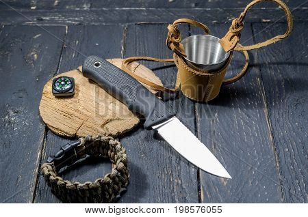 The Sharpest Knife Of A Hunter. A Compass And A Metal Mug.