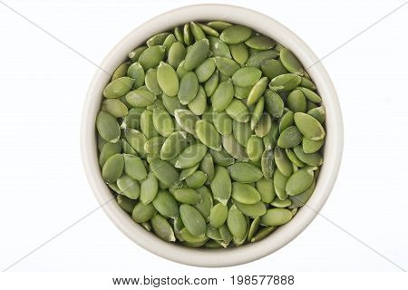 Shelled pumpkin seeds in a pot isolated on white background high in fibre and protein