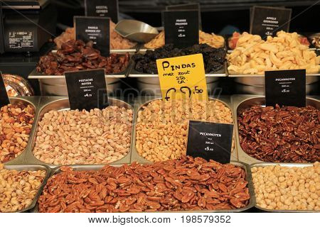Fresh nuts on a market stall (text on tags: names and prices of various nuts in Dutchpecan nuts peanuts pistacho para and cashew)