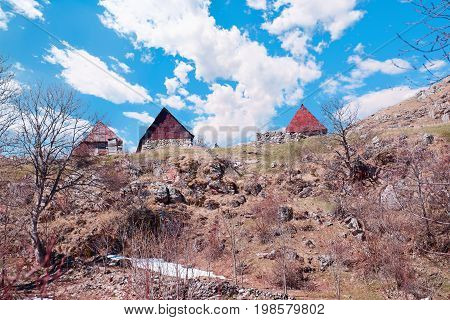 Traditional Old wooden hut in mountains of Bosnia and Herzegovina. The Village is Gradina and used as pasture in the summer for sheep. Mount Treskavica in background