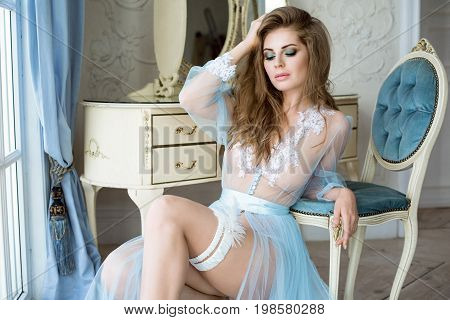 Beautiful sexy lady in elegant blue robe. Close up fashion portrait of model indoors. Beauty blonde woman in garter. Attractive female body in lace lingerie. Closeup naked girl in underwear