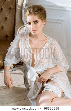 Beautiful sexy lady in elegant white robe. Close up fashion portrait of model indoors. Beauty blonde woman in garter. Attractive female body in lace lingerie. Closeup naked girl in underwear