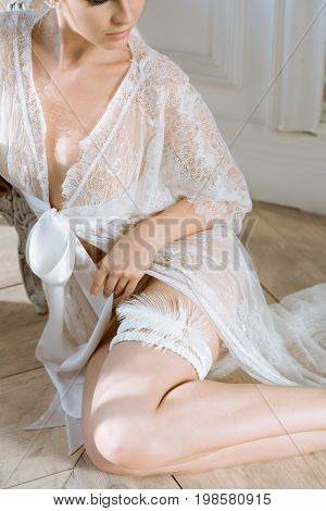 Beautiful sexy lady in elegant white robe and garter. Close up female fashion portrait of model indoors. Beauty woman with attractive body in lace lingerie. Closeup naked girl in underwear