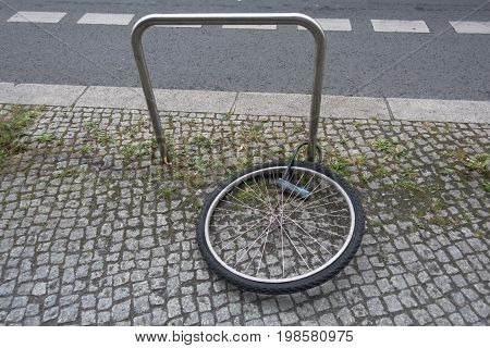 Bicycle theft on the street, bike stolen and only wheel with padlock left on the street