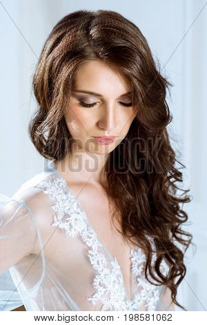 Fashionable female portrait of cute lady in blue robe indoors. Close up beautiful sexy model girl in elegant pose. Closeup beauty brunette woman with hairstyle and makeup. Glamorous face with make up