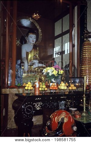 SINGAPORE / CIRCA 1990: Fruits and flowers are displayed upon an altar in front of a sculpture of the Buddha, in the Kwan Im Thong Hood Cho Temple.