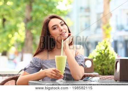 Pretty young woman drinking smoothie in cafe