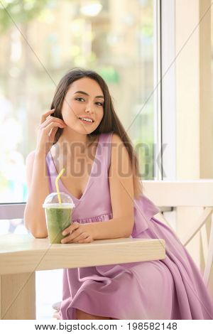 Romantic young lady enjoying tasty smoothie in cafe