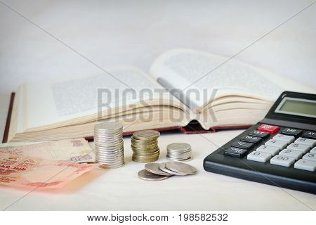 Cash Notes, Stacks Of Coins And A Calculator In Front Of An Open Book. The Concept Of Expensive Educ
