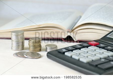 Coins Stacked Pile, Calculator, Open Book Light Background. Calculation Of Financial Stability And B