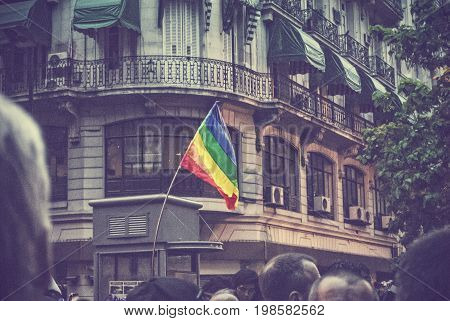Rainbow flag is swinging with a building in the background over people at gay pride in Buenos Aires, Argentina