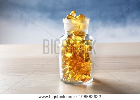 Glass bottle with fish oil capsules on wooden table