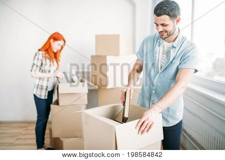 Young man unpacking cardboard boxes, housewarming