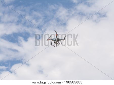 white drone hovering in a bright blue sky, clouds on front