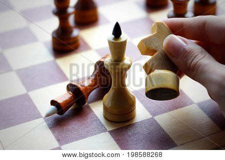 Hand Holding Wooden Chess Set On Chess Board. Chess. Black And White. Closeup
