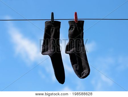 Black Socks Hang Drying On The Clothesline With Clothespins. Closeup. On The Background Of Blue Sky