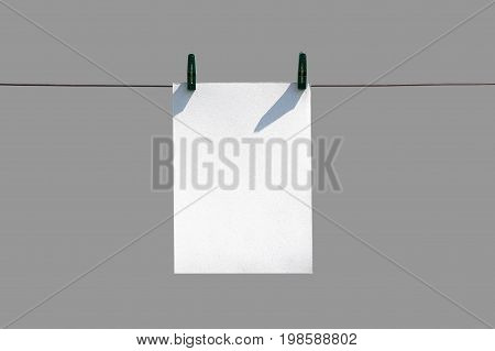 The White Piece Of Paper Hanging On Rope With Clothespins. Closeup. Isolated On Gray Background
