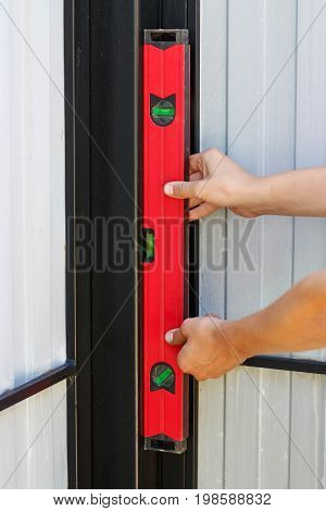 A Man Checks A Smooth Surface Level. Red Construction Level